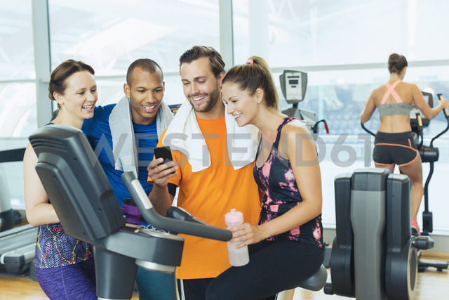 Smiling friends using cell phone at exercise bike in gym - CAIF11785 - Robert Daly/Westend61