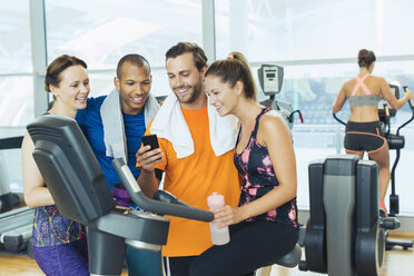 Smiling friends using cell phone at exercise bike in gym - CAIF11785