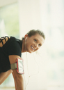 Smiling woman with headphones and mp3 player armband at gym - CAIF11788