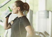 Woman resting and drinking water at gym - CAIF11791