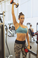 Focused woman lifting dumbbell overhead at gym - CAIF11797