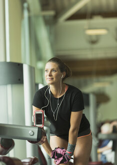 Woman with headphones stretching leg at gym - CAIF11800