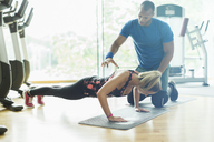 Personal trainer guiding woman doing push-ups at gym - CAIF11806