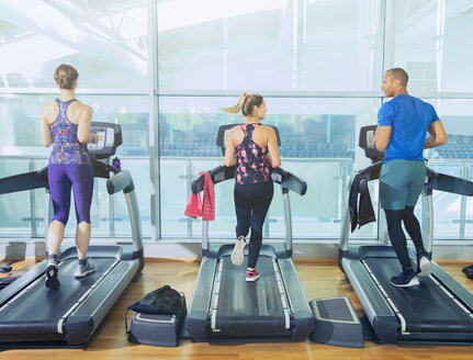 Man and women running on treadmills at gym - CAIF11809