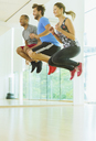Enthusiastic men and woman jumping in exercise class - CAIF11812