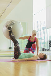 Personal trainer guiding woman with fitness ball between legs - CAIF11815