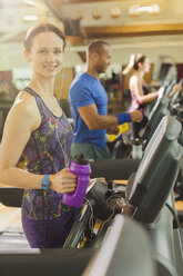 Portrait smiling woman with water bottle on treadmill at gym - CAIF11821