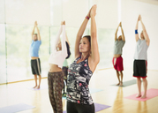 Yoga class with arms raised - CAIF11824