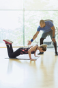Personal trainer guiding woman doing push-ups on knees at gym - CAIF11830