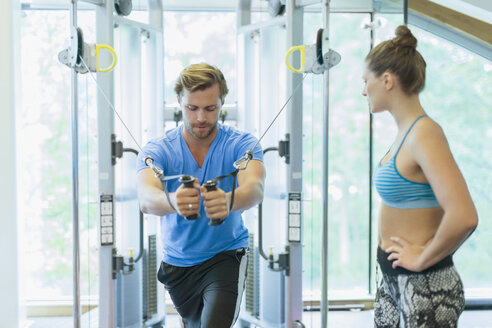 Personal trainer guiding man using cable exercise machine at gym - CAIF11836