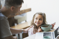 Father and daughter eating breakfast at laptop - CAIF11839