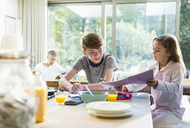 Brother and sister eating breakfast and doing homework - CAIF11842