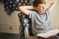 Confident boy doing homework with hands behind head - CAIF11848