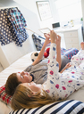 Brother and sister taking selfie on bed with digital tablet camera - CAIF11860