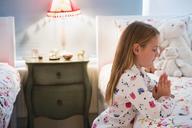 Girl in pajamas saying bedtime prayers at bed - CAIF11878