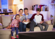 Family eating popcorn and watching TV in living room - CAIF11884