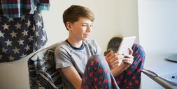 Boy in pajamas using digital tablet in bedroom - CAIF11896