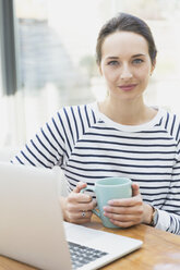 Portrait confident woman drinking coffee at laptop - CAIF11908