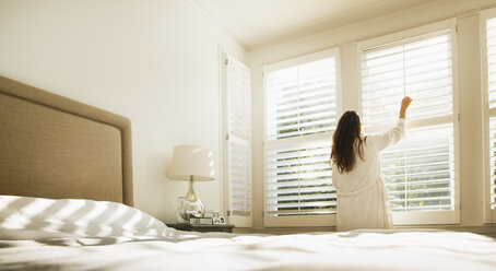 Woman in bathrobe opening bedroom window blinds - CAIF11911