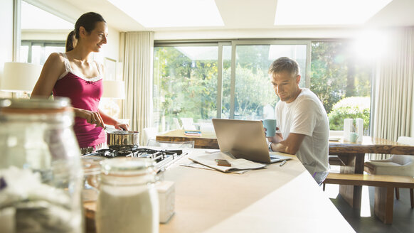 Couple cooking and working at laptop in morning kitchen - CAIF11914