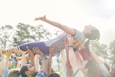 Carefree woman crowdsurfing supported by team - CAIF11920