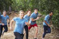 Smiling team running on boot camp obstacle course - CAIF11923
