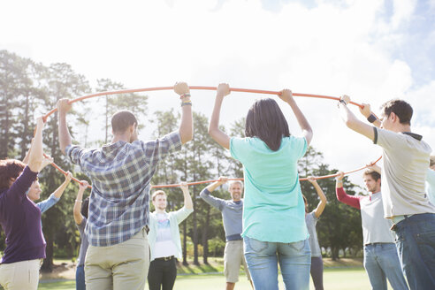 Team forming connected circle with plastic hoop in sunny field - CAIF11932