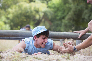 Teammate helping man crawling on boot camp obstacle course - CAIF11941