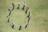 Team connected in circle by plastic hoops in sunny field - CAIF11950