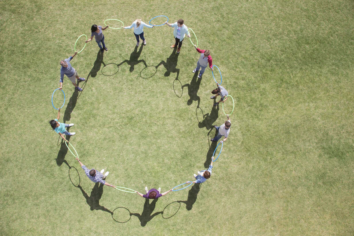 Team connected in circle by plastic hoops in sunny field - CAIF11950 - Martin Barraud/Westend61