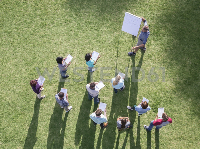 Businessman leading meeting at flipchart in sunny field - CAIF11956 - Martin Barraud/Westend61