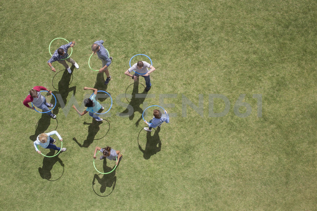 People spinning in plastic hoops in sunny grass - CAIF11968 - Martin Barraud/Westend61