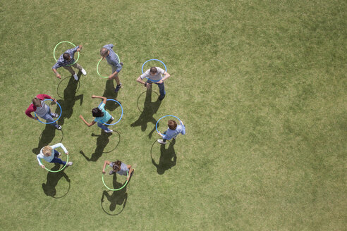 People spinning in plastic hoops in sunny grass - CAIF11968