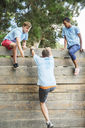 Teammates helping man over wall at boot camp obstacle course - CAIF11977