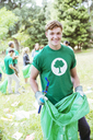 Portrait of smiling environmentalist volunteer picking up trash - CAIF11992