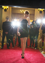 Celebrity in black dress being photographed by paparazzi photographers at red carpet event - CAIF12028
