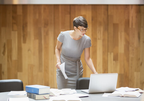 Businesswoman working at laptop in office - CAIF12061