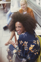 Portrait enthusiastic woman with afro at sidewalk cafe - CAIF12091