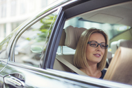 Businesswoman reading newspaper in back seat of car - CAIF12112