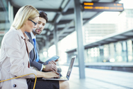 Business people using laptop at train station - CAIF12121