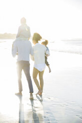 Family walking on beach in sunlight - CAIF12133