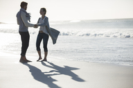Young couple holding hands on beach - CAIF12139