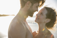 Young couple looking at each other on beach - CAIF12142