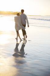 Young couple holding hands and walking on beach at sunset - CAIF12151