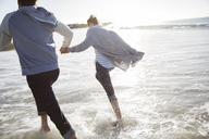 Young couple holding hands and running on beach - CAIF12154
