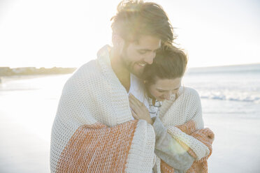 Young couple wrapped in blanket on beach - CAIF12157