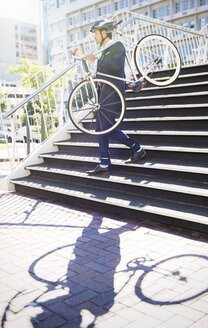 Businessman in suit and helmet carrying bicycle down urban stairs - CAIF12172