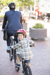 Portrait smiling boy riding tandem bicycle with businessman father - CAIF12175