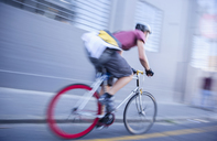 Bicycle messenger speeding down urban street - CAIF12178
