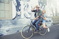 Portrait playful couple riding bicycle along urban graffiti wall - CAIF12184